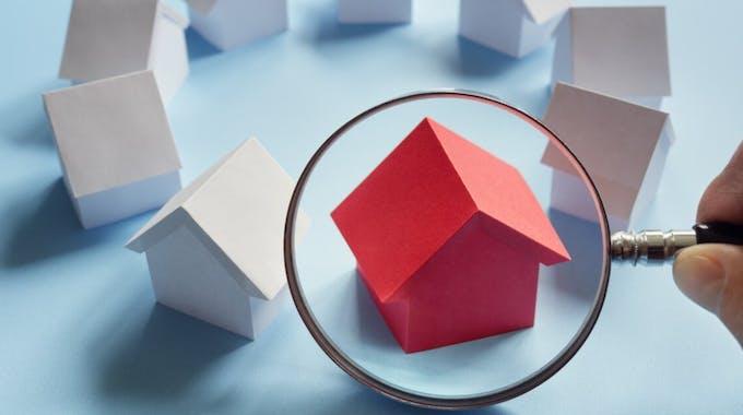 rotes Papierhaus neben mehreren weißen Papierhäusern mit Lupe