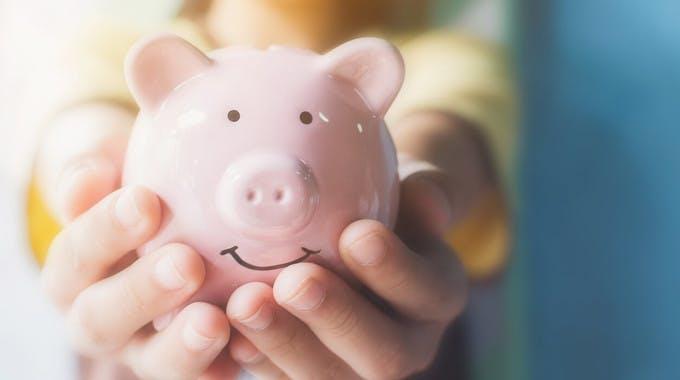 Kinderhände halten lächelndes Sparschwein