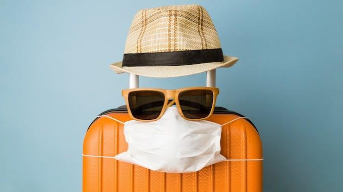 Reisekoffer, Sonnenhut, Sonnenbrille und Maske