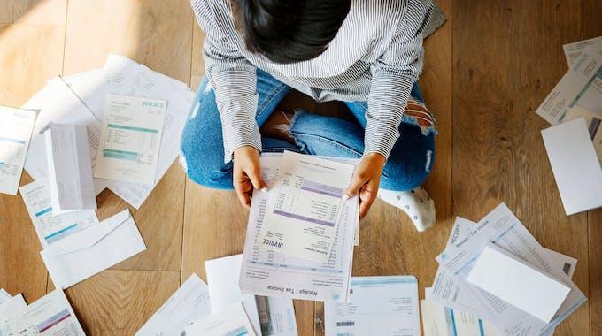 Frau sitzt auf dem Boden und sortiert Unterlagen
