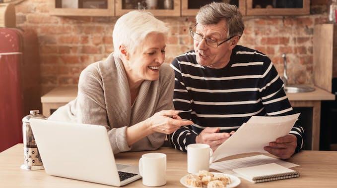 Glückliche Rentner am Tisch mit Laptop bei Finanzplanung