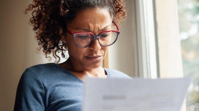 Besorgte Frau mit Brief neben Fenster