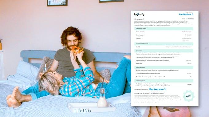 junges Paar liegt auf Bett und isst Pizza, bonify Mieterauskunft