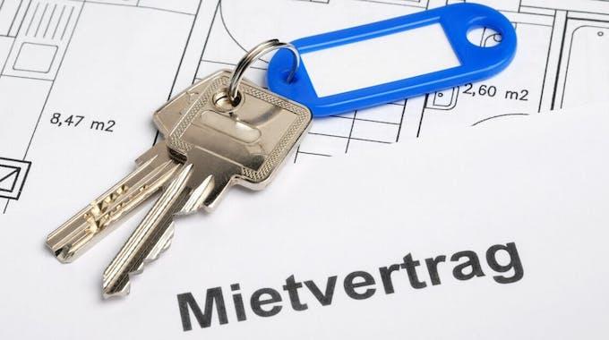 Hausschlüssel mit Mietrvertrag und Bauplan