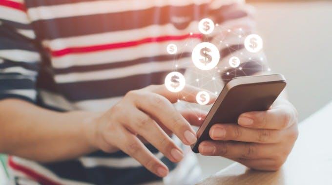 Junger Mann leiht sich Geld über sein Handy