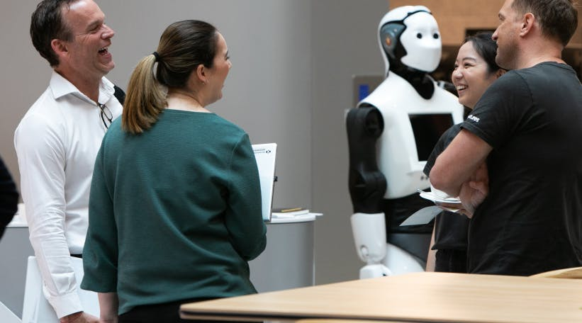 Guests and people chatting next to Chip the robot