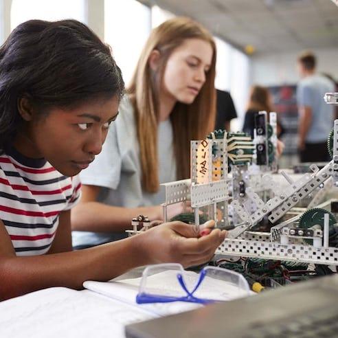 Students building a machine on desktop