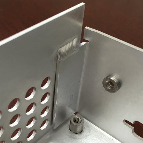 Sheet metal part with inserts and welds