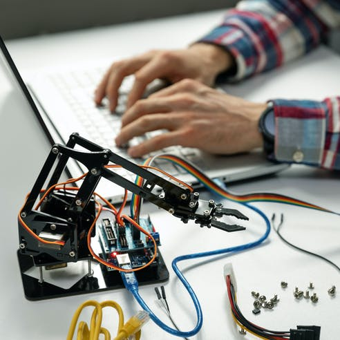 man typing with small robot next to him