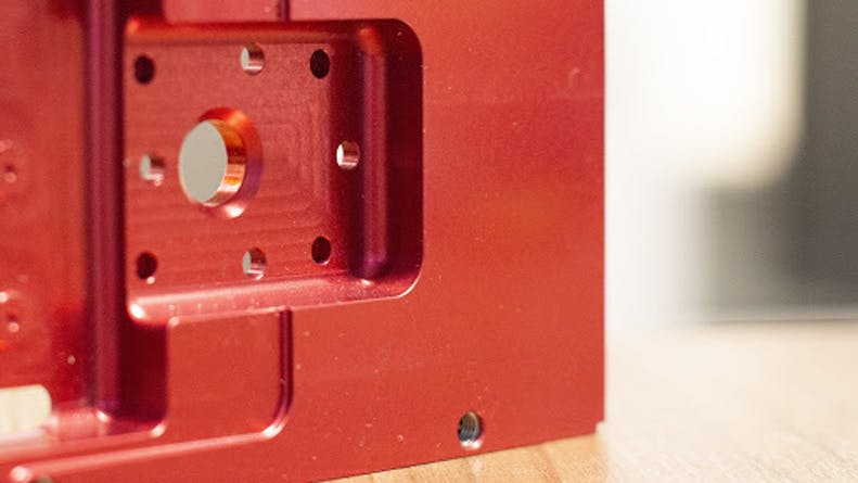An aluminum CNC machined part with a red anodize finish