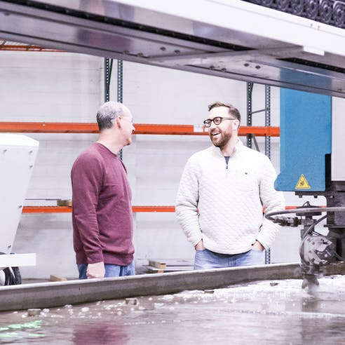 The Xometry Supplies team by a waterjet