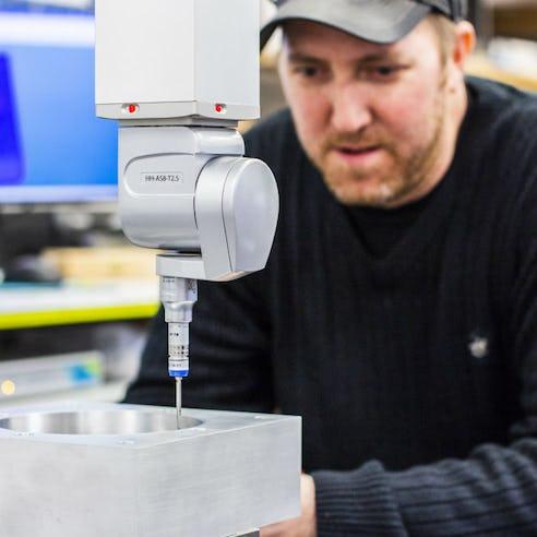 Xometry technician operating a CMM machine