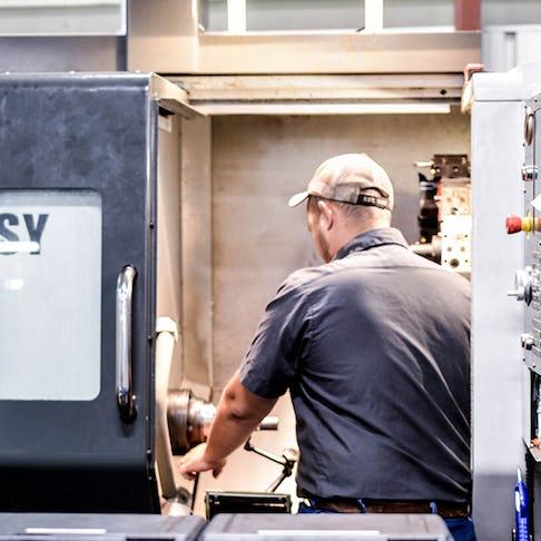 A CNC machinist using a live tooling lathe