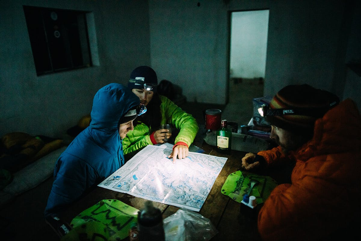Thomas Woodson and Carston Oliver look over a topography map lit by headlamp.