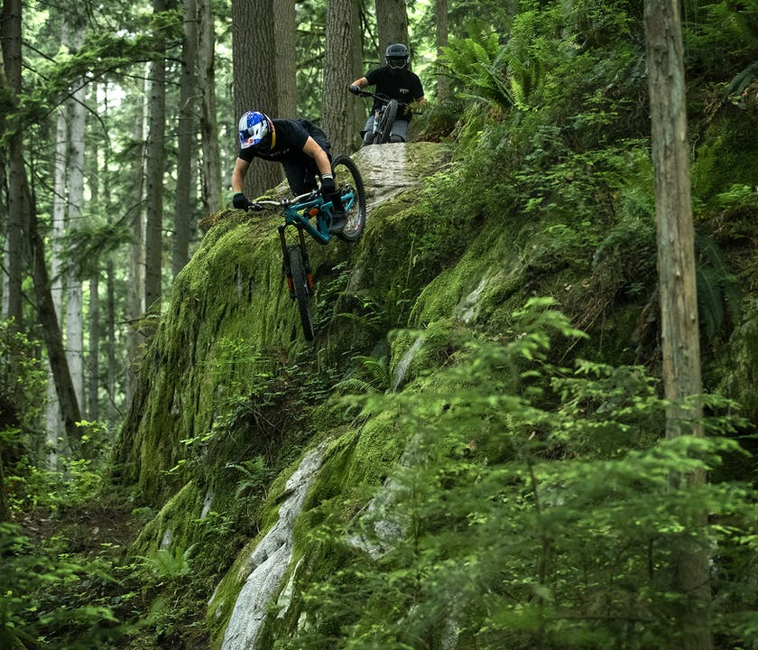 Richie Rude riding a steep rock face on the SB165 with Stu Dickson following behind.