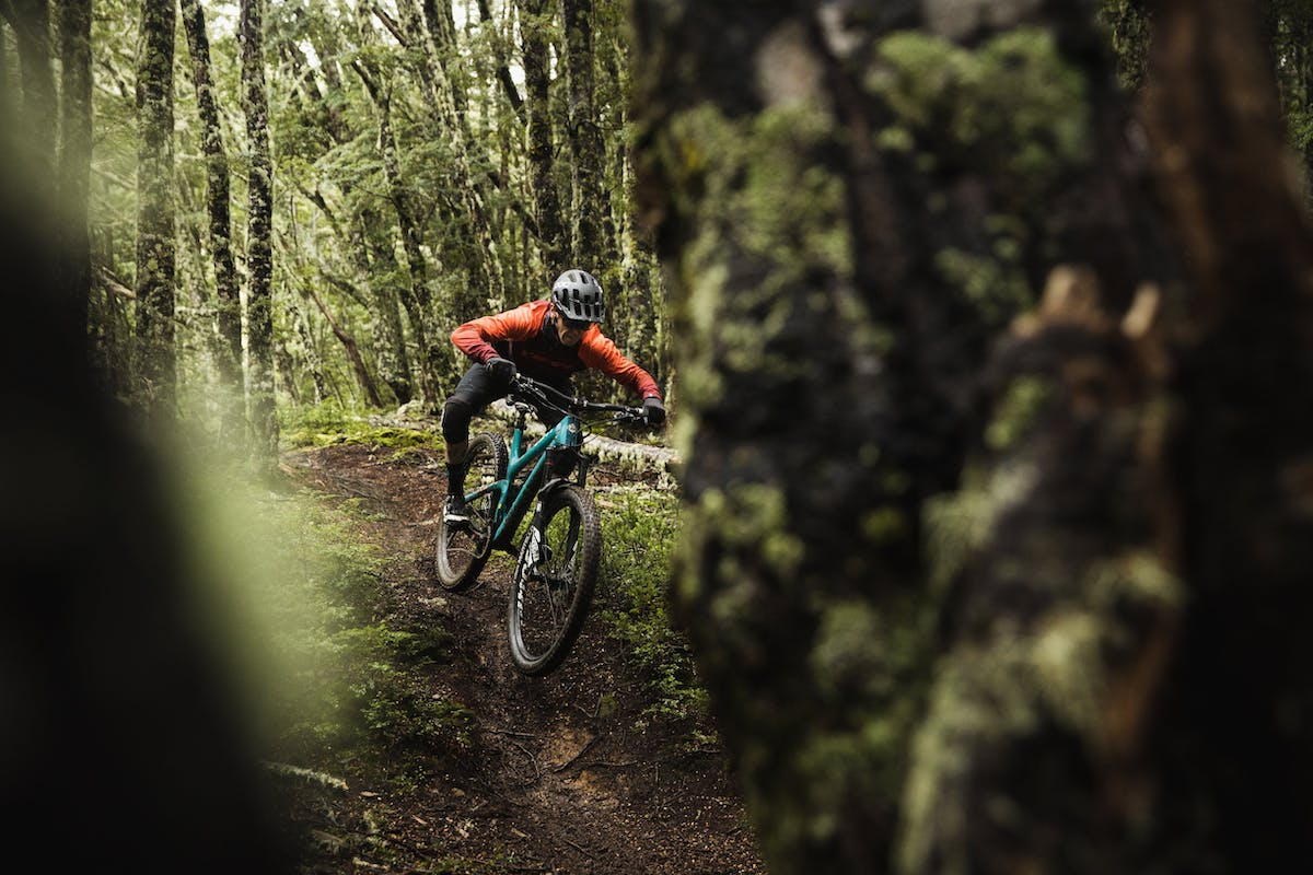 Tom Sampson riding through a moss covered forest.