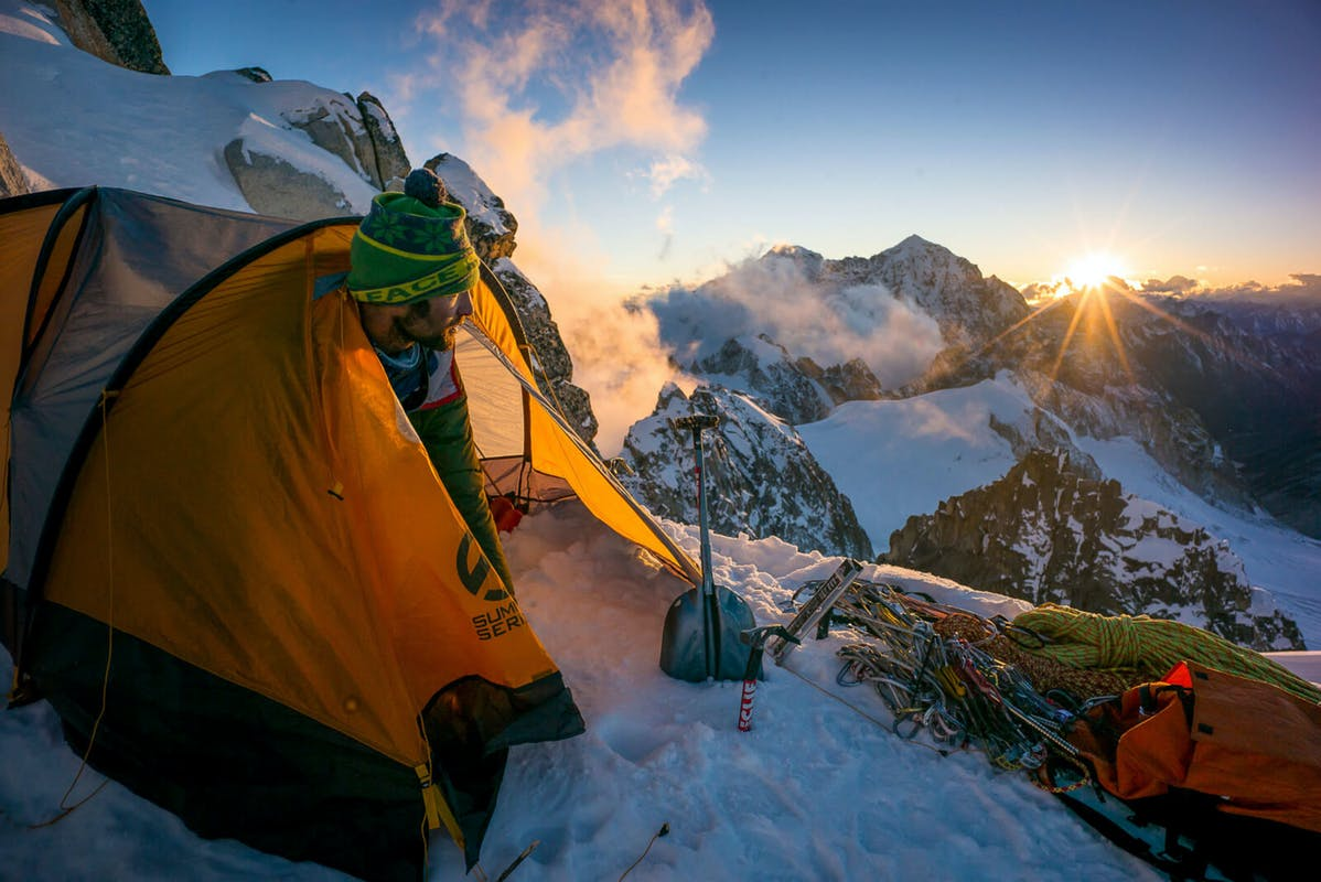 Renan Ozturk emerging from his tent at sunrise