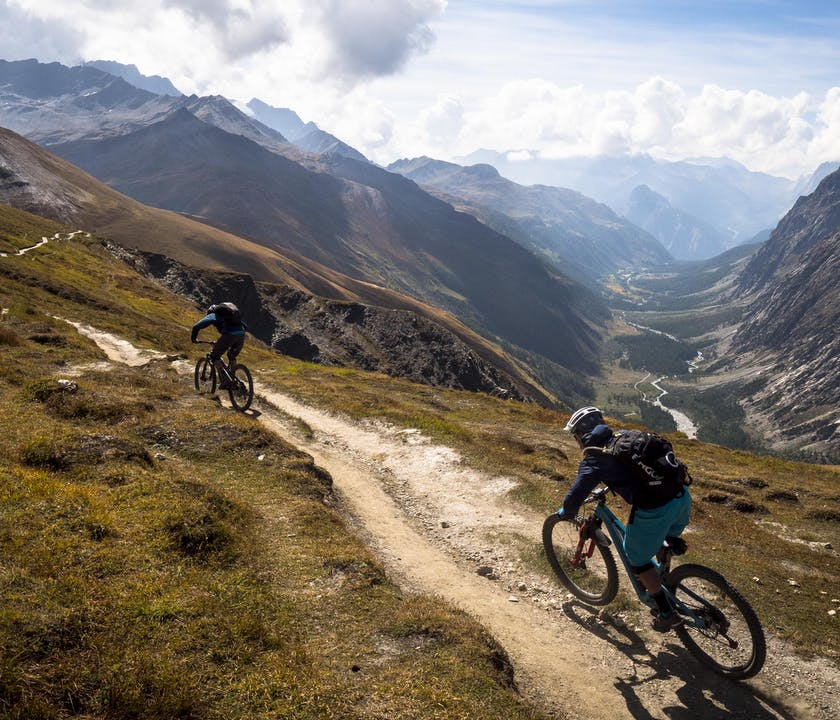 Nate Hills and Francesco Gozio riding singletrack above the valley