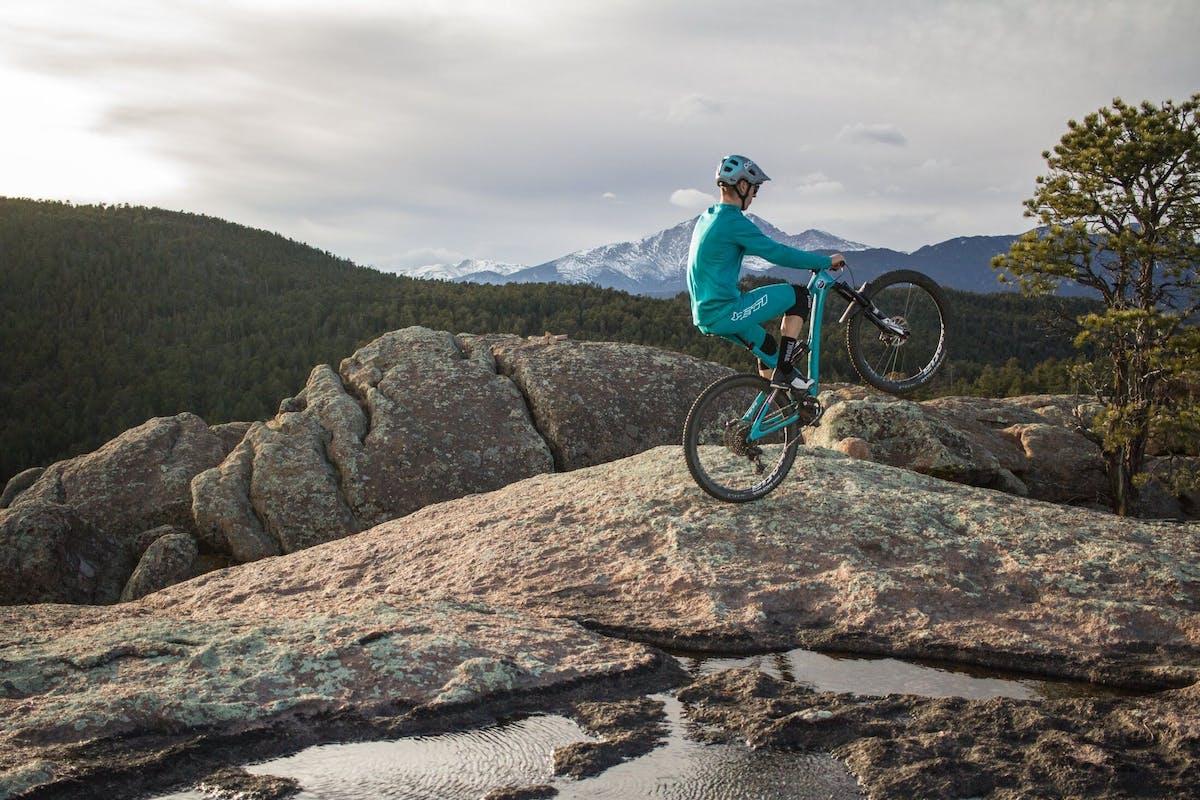 Tom Sampson riding a wheelie on a rock slab