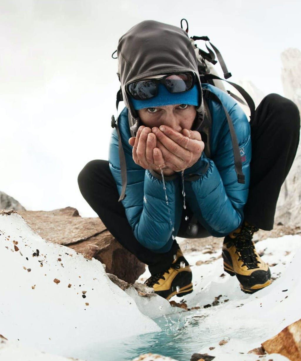 Renan Ozturk sipping water from glacial runoff