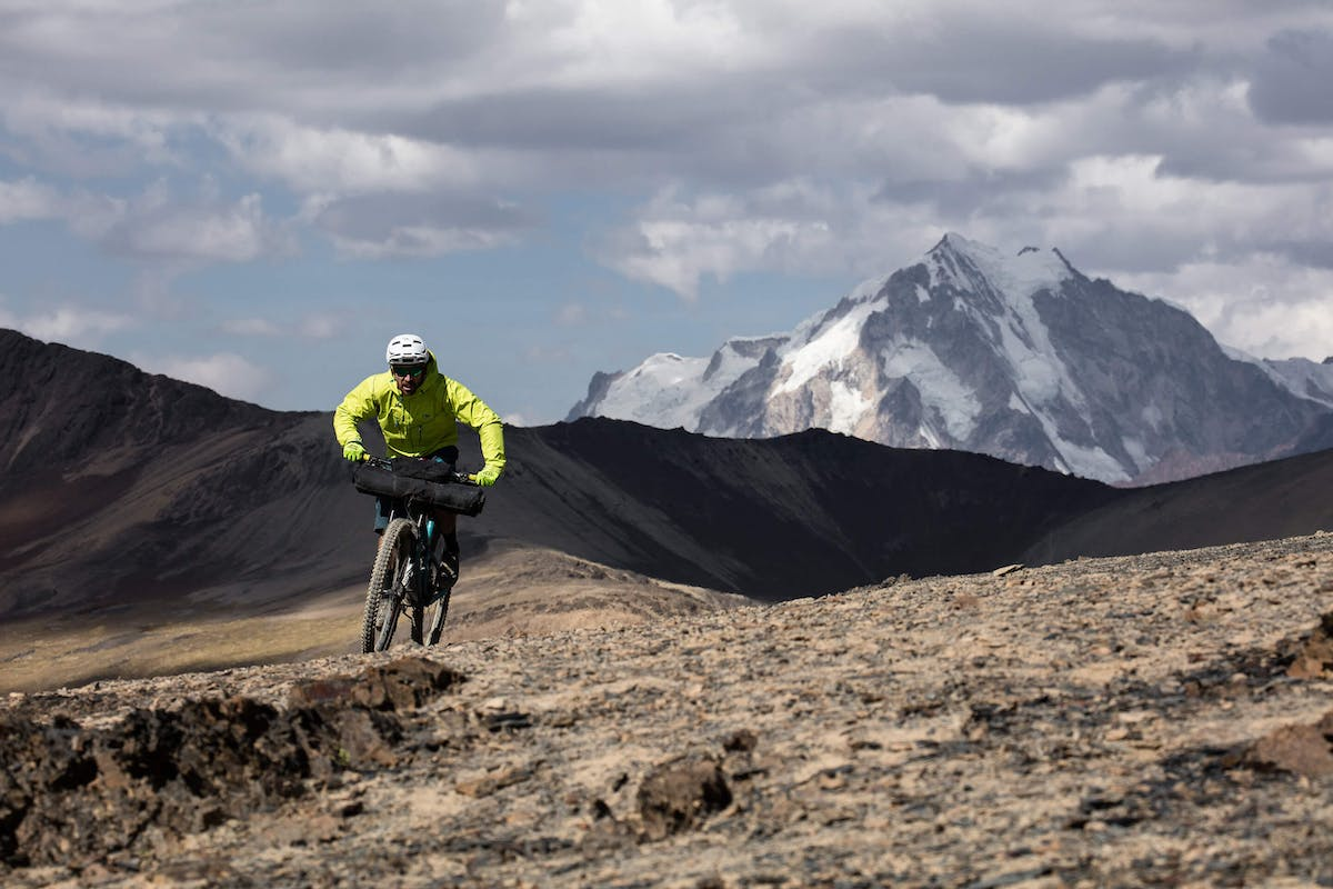 Nate Hills pedals single track on his Yeti SB5.5 with snow capped mountain peaks in the background