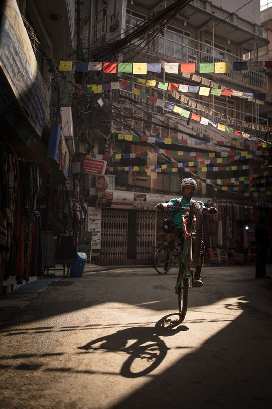 RJ Ripper riding a wheelie through the streets of Kathmandu