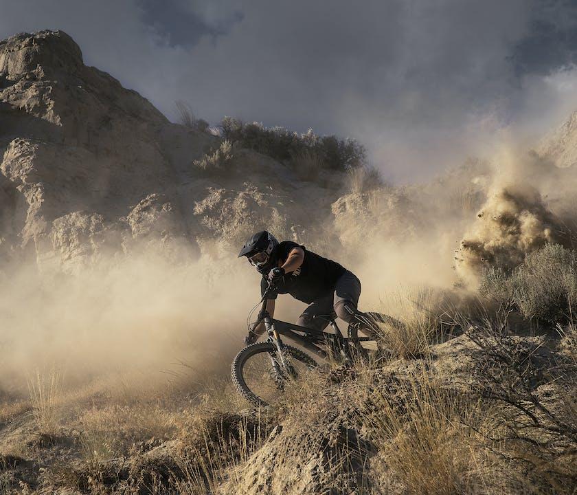Stu Dickson riding through the dust on a Yeti SB165