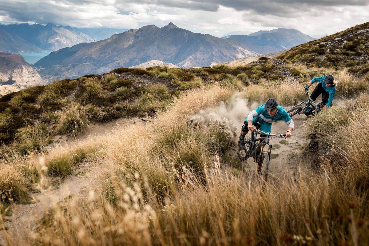 Richie Rude and Cody Kelley hit the turn on winding single track in the grassy dry land of New Zealand
