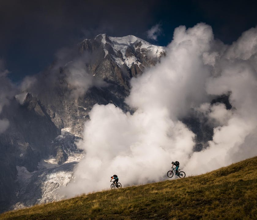 NATE HILLS and FRANCESCO GOZIO riding down a ridge line.