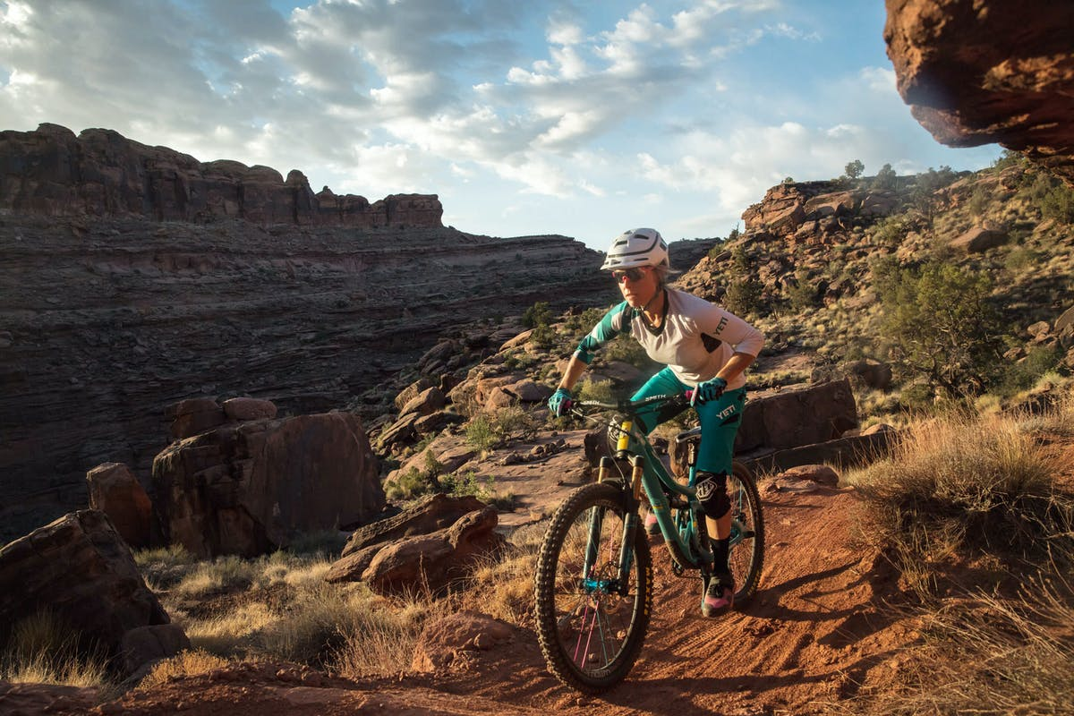 Liz Cunningham pedaling with classic Moab views in the background