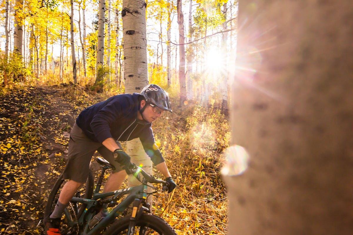 Jim Harris riding through aspen trees