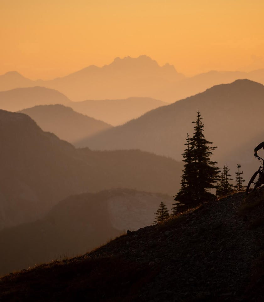 Marty Lazarski riding at sunset with layers in the distance