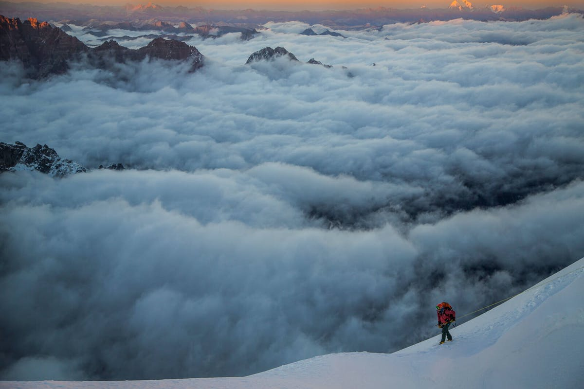Renan Ozturk climbing above the clouds