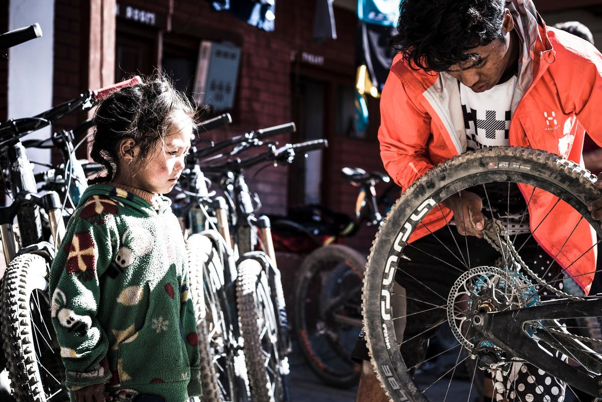 RJ fixes his bike while a young girl watches
