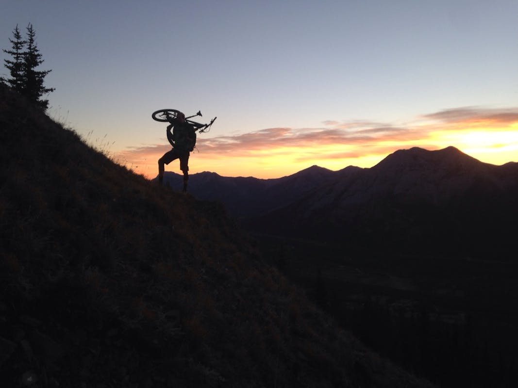 Reuben Krabbe hiking his bike in the alpine at sunset