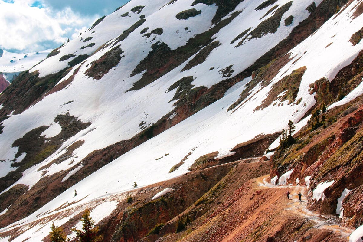 Riders traversing a high alpine road.