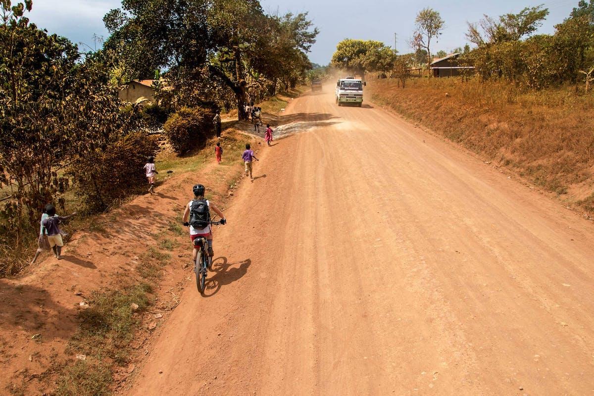 Nichole Baker with kids running beside her in Uganda