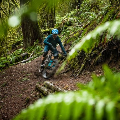 Geoff Kabush riding the SB100 in a lush forest.