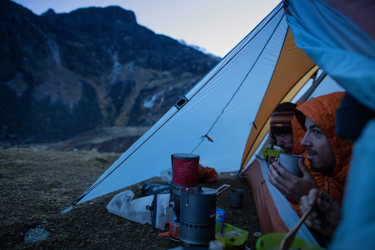 Thomas Woodson and Nate Hills sipping coffee in tent  at base camp