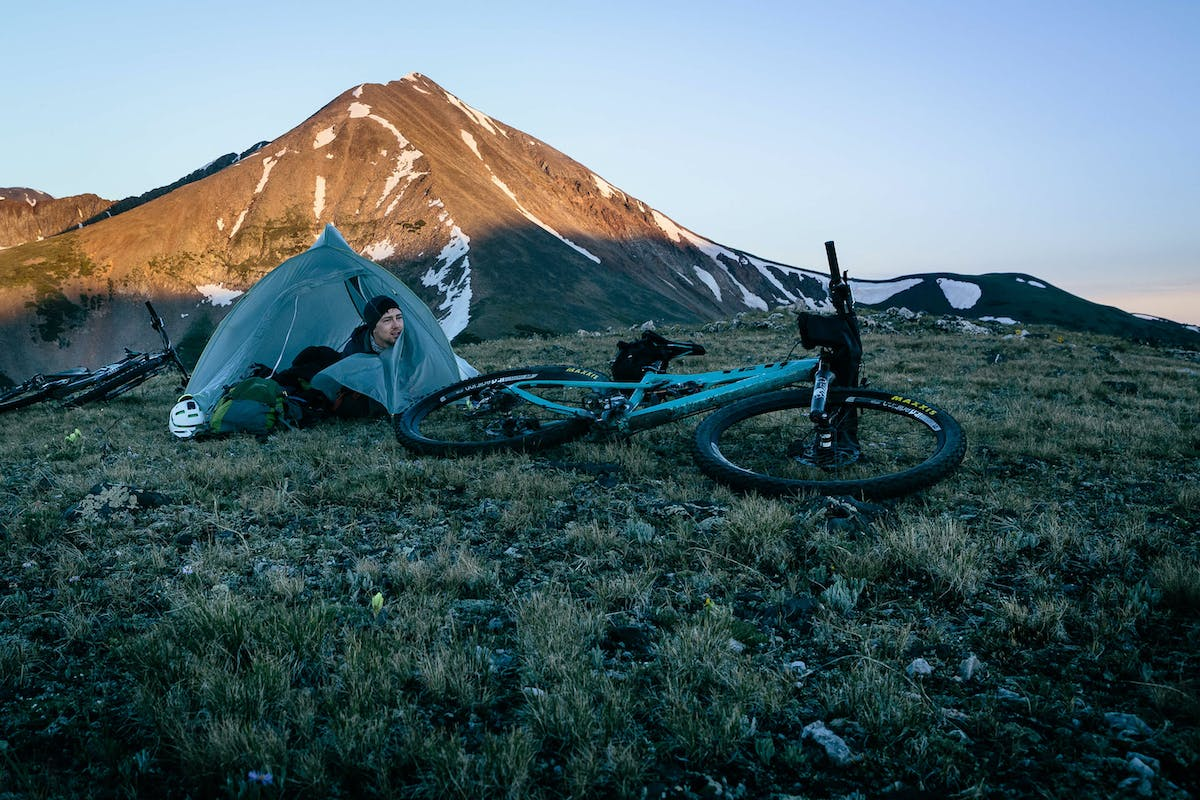 Sam Seward emerging from his tent at sunrise on the Colorado Trail