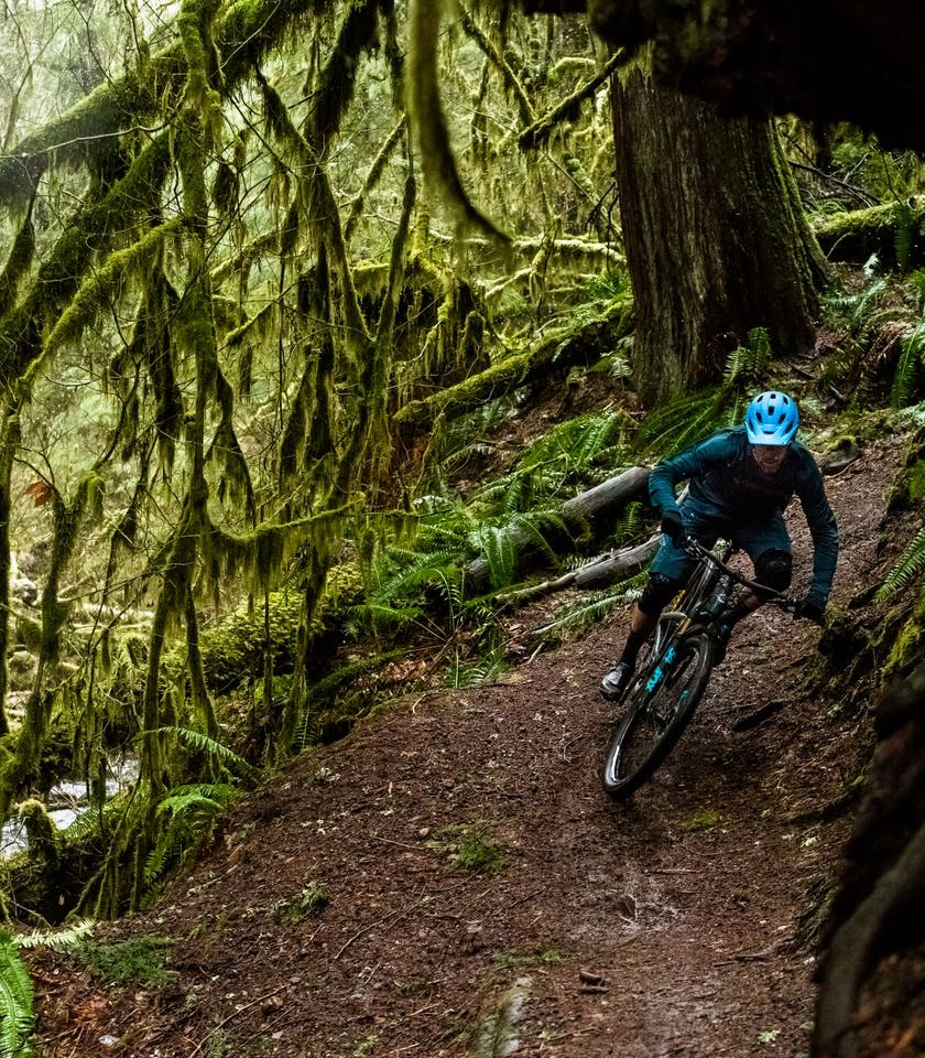 Geoff Kabush carving through a moss covered forest