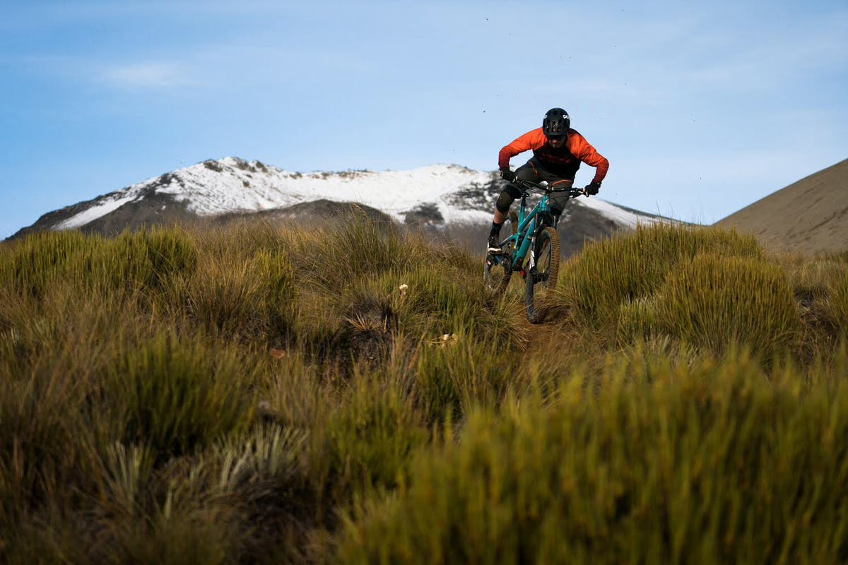 Tom Sampson riding tight, grassy single track with a mountain in the background