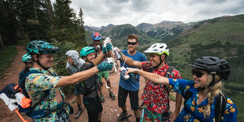 A group of riders cheersing on a trail