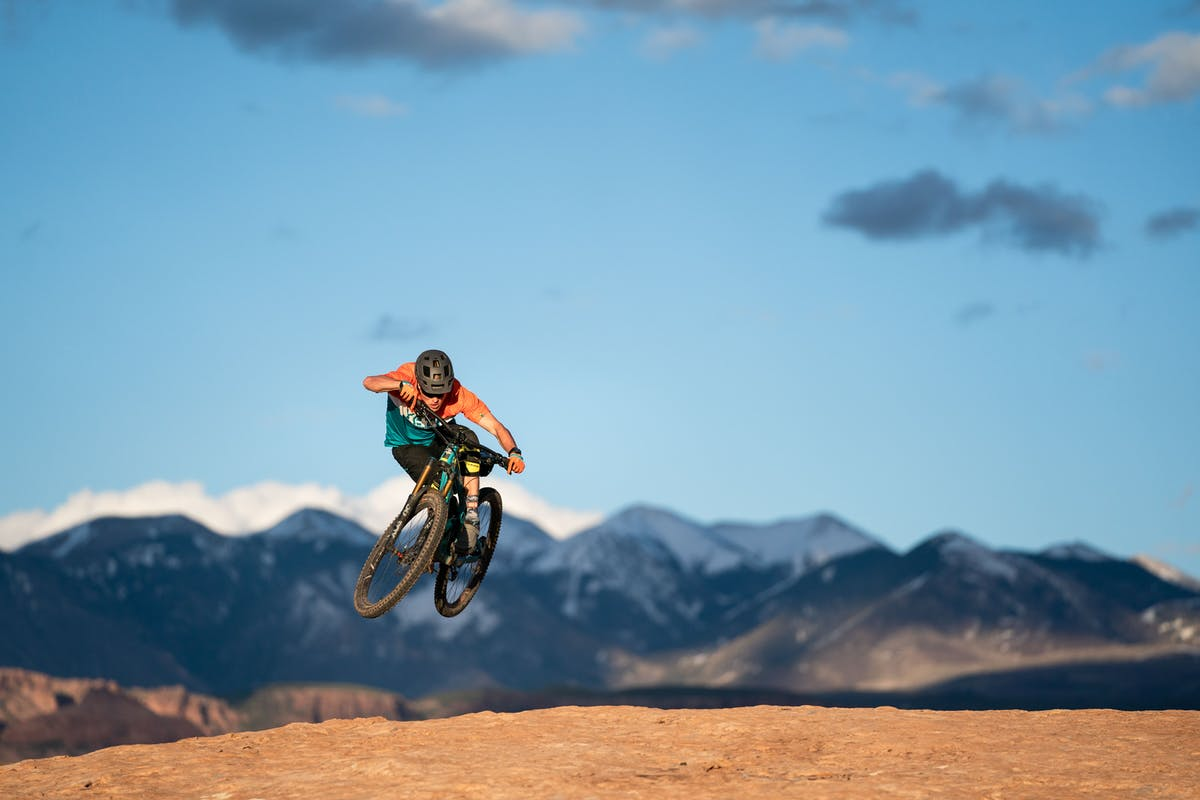 Marty Schaffer catching air over slick rock with the La Sal mountains in the background.