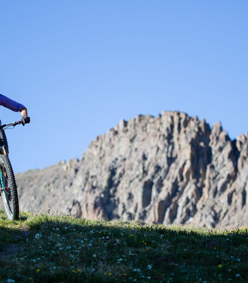 NIchole Baker riding high above treeline with jagged mountains in the background.