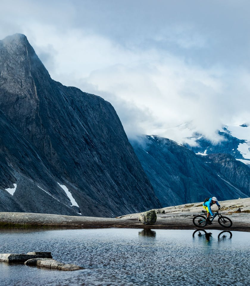 Joey Schusler on the edge of an apline lake with classic Norwegian mountains in the background.