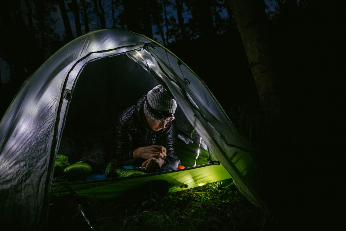 Justin Reiter settling into a illuminated tent off the Colorado Trail for the night