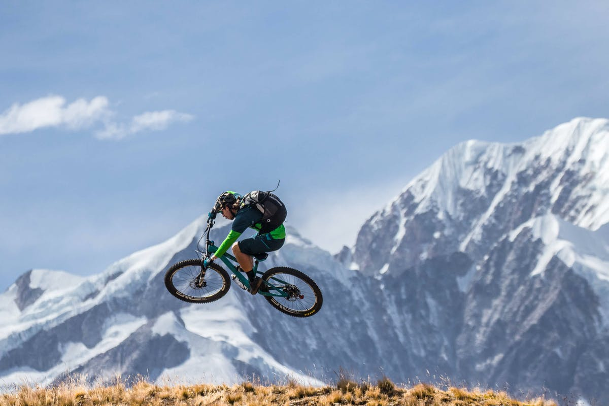 Joey Schusler hitting a jump with largoe Bolivian peaks in the background