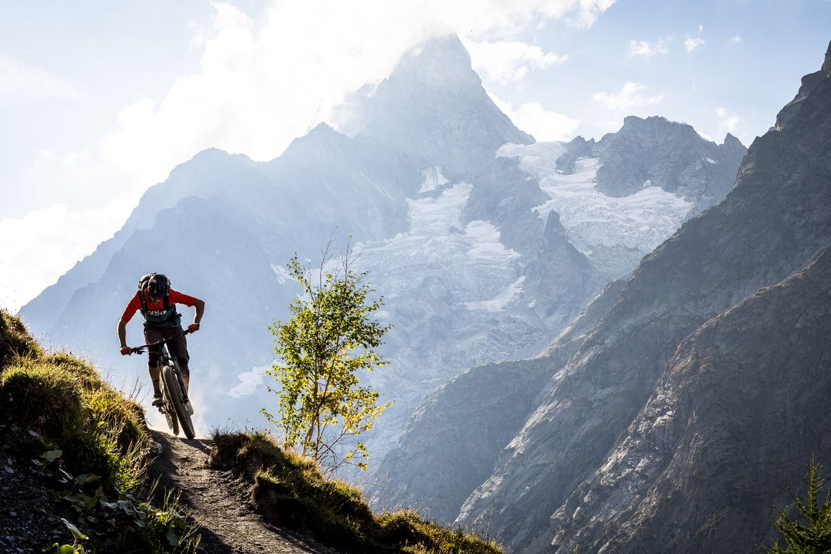 Francesco Gozio riding thing single track with Mt. Blanc in the background.
