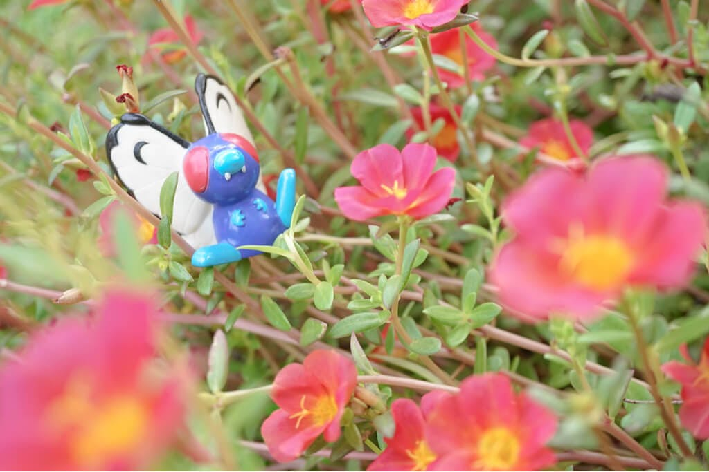 A butterfree Pokemon figure in a flower patch